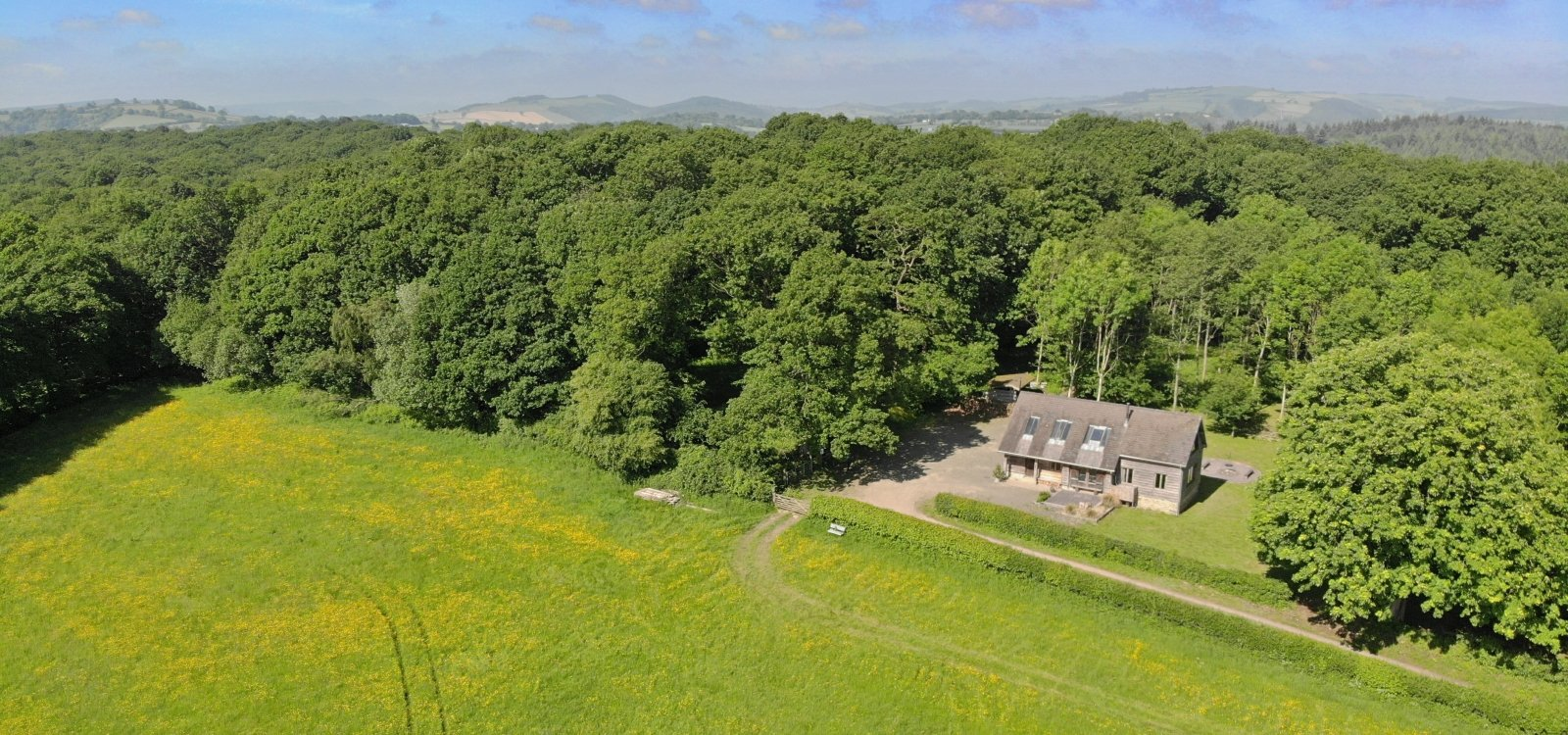 an aerial view of the timber-framed building in a secluded setting surrounded by woodland and fields