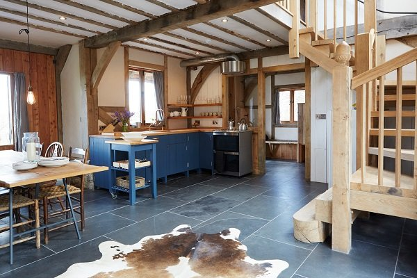 Oak beams surround an open plan kitchen area