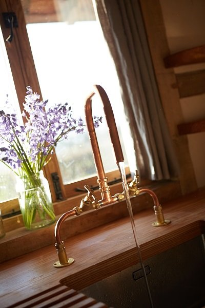 A kitchen tap made of copper sits in the barn kitchen with wooden worktop