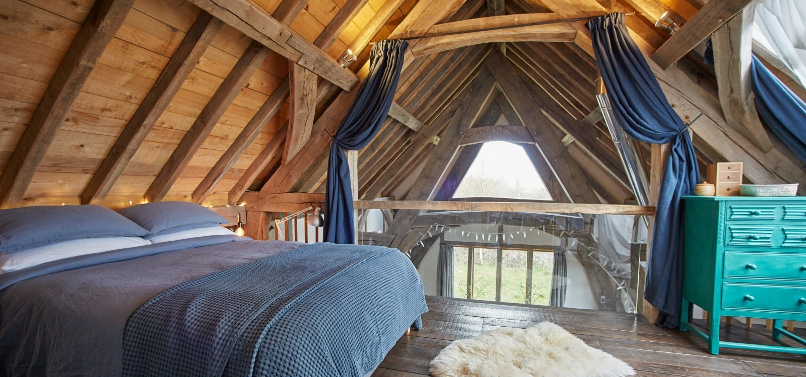 a comfortable double bed creates quality accommodation under oak beams