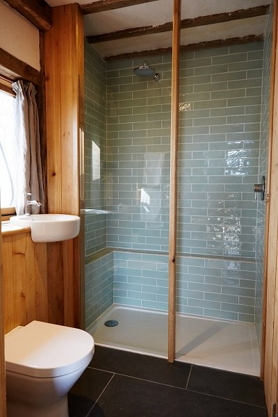A bespoke walk-in shower, surrounded by timber beams, is available on the ground floor of the accommodation